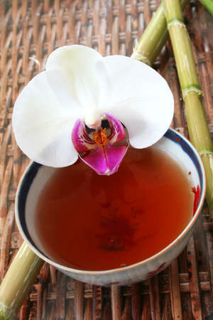 assam tea: Tea in antique Chinese bowl with bamboo and orchid flower