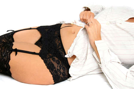 suspenders: Woman wearing stockings and suspenders putting on shirt on bed