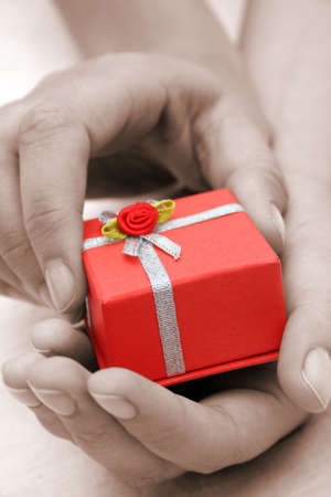 Sepia hands holding red gift box photo