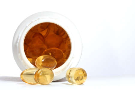 Yellow capsules and white pill box Stock Photo