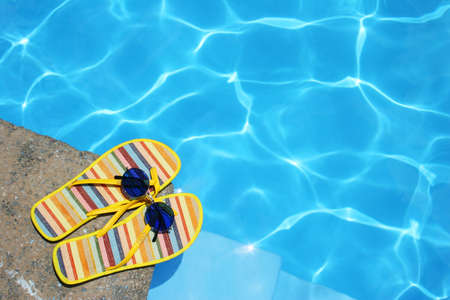 Bright Flip-flops and sunglasses by swimming pool Stock Photo - 416548