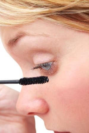 Woman putting on mascara photo