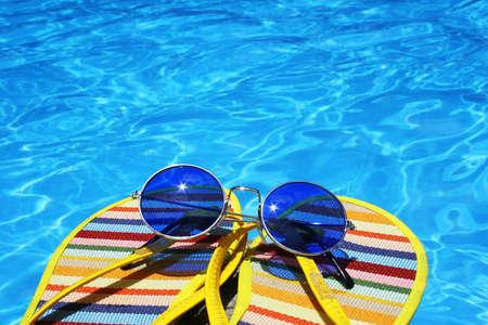 feat: Chancletas y gafas de sol por el azul brillante piscina de agua Foto de archivo