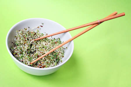 macrobiotic: Fresh spouts in bowl with chopsticks and green background Stock Photo