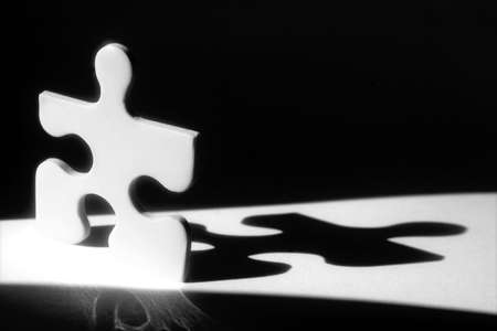 White jigsaw piece in beam of light with shadow behind Stock Photo