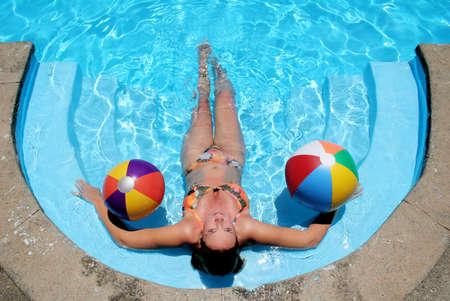 Woman sunbathing in still blue pool with beach balls Stock Photo