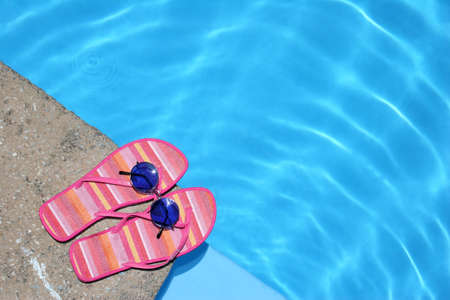 anniversary beach: Pink flip-flops and sunglasses by blue pool Stock Photo