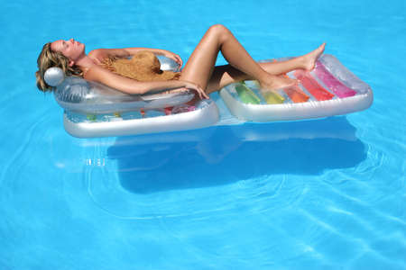 Woman on lilo floating in blue pool Stock Photo - 434152