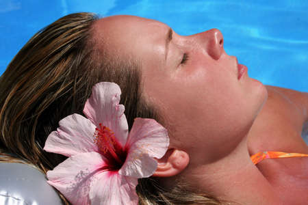 Woman sunbathing by pool with flower
