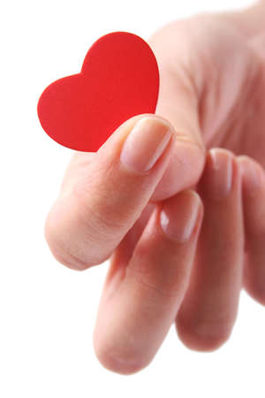 Womans fingers holding red heart
