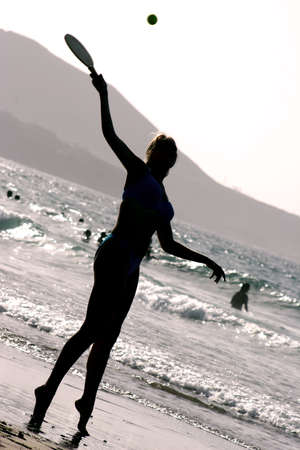 Silhouette of woman playing beach tennis at sunset photo