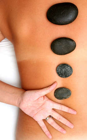 restore energy flow: Woman with massage pebbles on her back Stock Photo