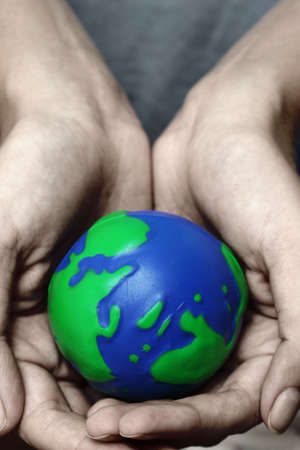 Cupped hands holding planet Earth photo
