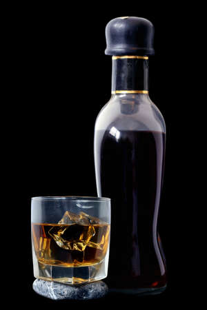 distilled: Glass of rum and bottle over black