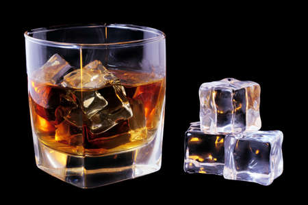tumbler: Whiskey in tumbler and ice cubes over black