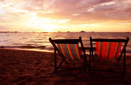 silla de madera: Dos tumbonas en la playa al atardecer  Foto de archivo
