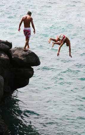 antics: Boys jumping into the sea from rocks Stock Photo