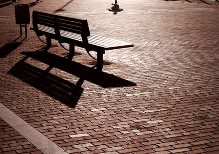 Bench on wide brick pathway at sunset