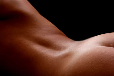nude black woman: Womans back with low lighting and black background Stock Photo