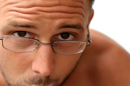 curiously: Man with glasses looking curiously at theviewer from up close