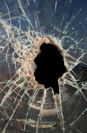 robbery: Hole smashed in thick,dirty glass with dark background