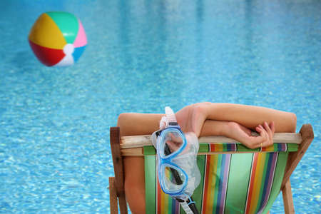 Woman in deckchair by blue pool with floating beachball photo