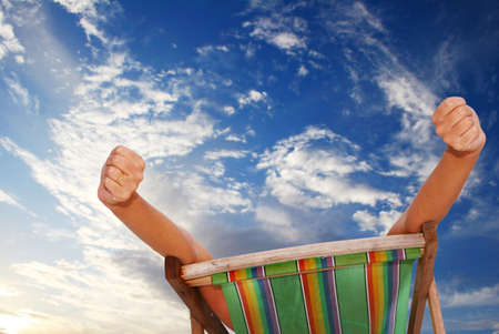 Woman stretching in deckchair with sunset sky behind her Stock Photo - 593168