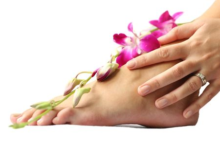 Womans foot and hand on white with orchid flowers photo