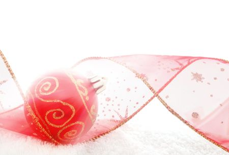 Red bauble and Christmas ribbon in bright beam of light photo