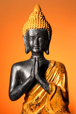 nirvana: Buddha sculpture at prayer with orange glow background