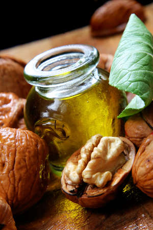 Small jar of natural oil with walnuts and green leaf Stock Photo