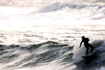 silhouetted: Surfer silhouetted through sea mist just after sunset Stock Photo