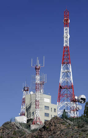 millitary: Red and white telecommunications masts on top of a hill