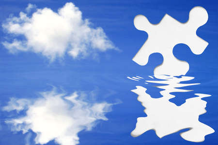 White jigsaw piece emerging out of water with blue sky background