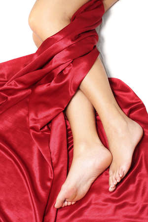 Pretty womans legs with luxury red silk sheet Stock Photo
