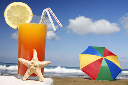 Tropical cocktail with starfish with parasol and beach photo