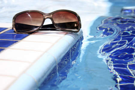 Sunglasses by bright swimming pool with mosaic pattern