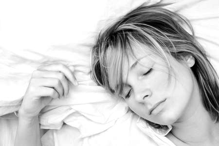 High key black and white image of pretty girl sleeping peacefully photo