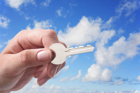 Woman's hand holding key with pretty sky background Stock Photo - 858175