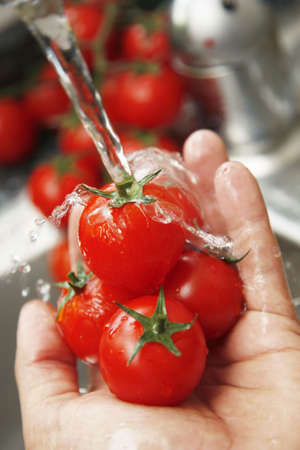shallow water: Washing tomatoes under the tap. Focus is shallow and on the point where water touches tomato Stock Photo
