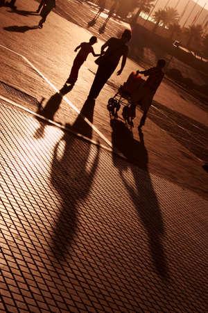 ni�os caminando: Mujer y dos hijos a pie a la puesta del sol