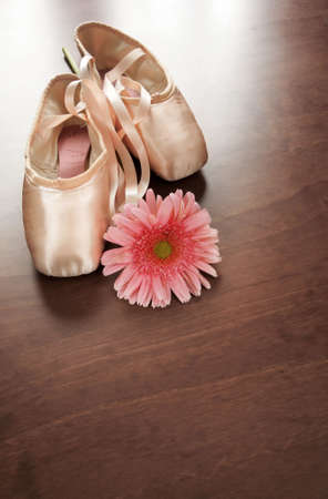 Pink satin ballet shoes on dark floor