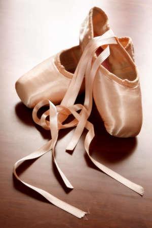 Pink satin ballet shoes on dark floor in slight soft focus Stock Photo