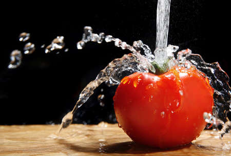 Fresh tomato under running tap with water drops