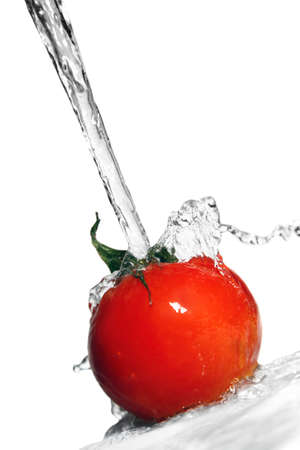 Fresh tomatos under running tap with water drops