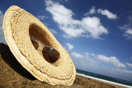 Summer hat and sunglasses on a sunny beach