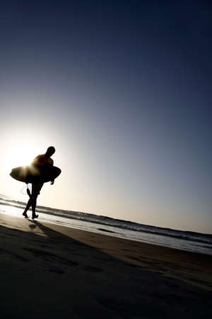 Surfer leaving the water in the late evening with the sun behind him Stock Photo