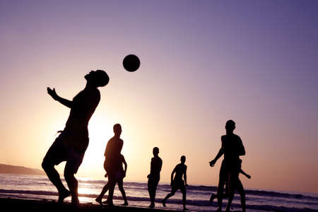 A game of football on the beach at sunset photo