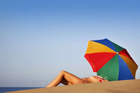 parasols: Pretty woman under parasol on the beach