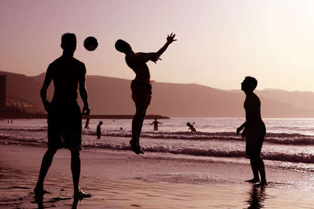 Group of boys playing football on the beach photo